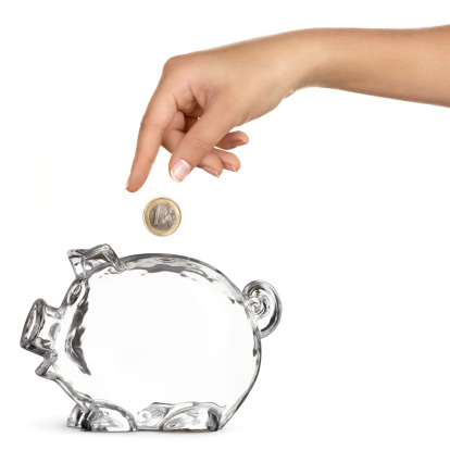 Concept of a woman dropping a Euro into an empty piggy bank - isolated over white