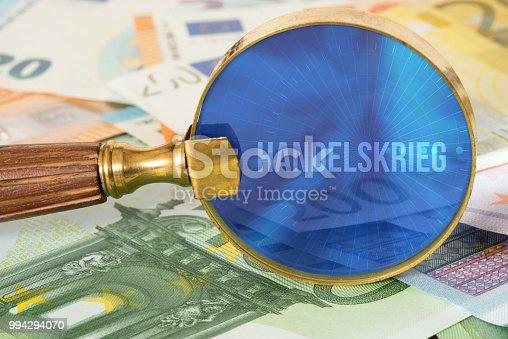 istock Euro Geldscheine, eine Lupe und Handelskrieg 994294070