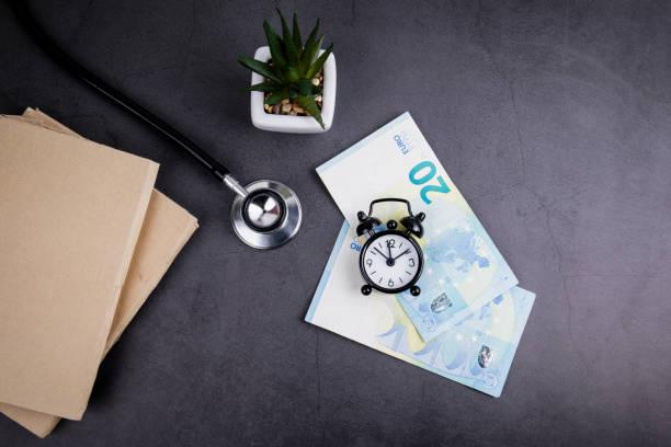 euro-geld und stethoskop auf betontisch - kindergeldantrag stock-fotos und bilder