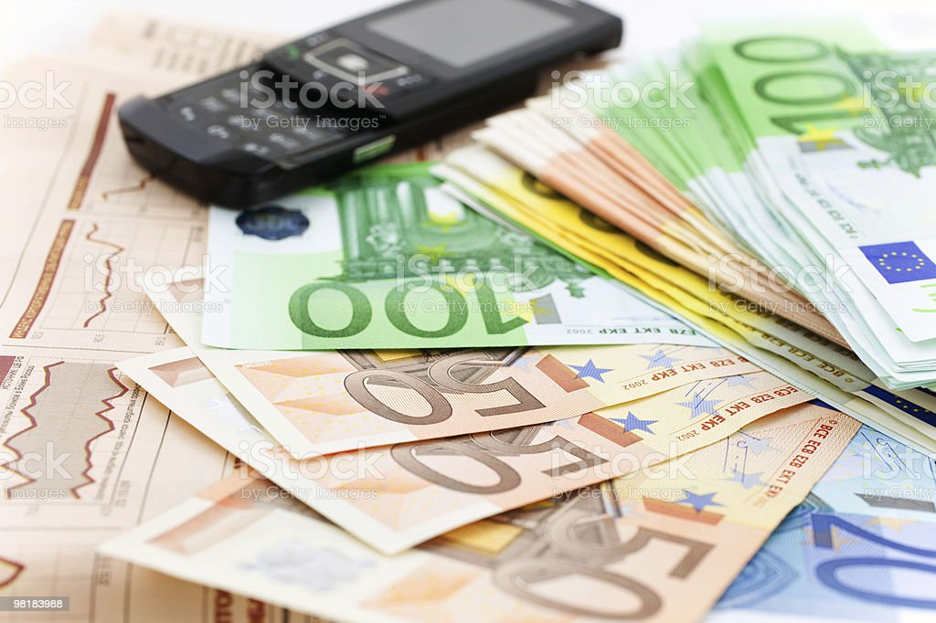 euro notes and black mobile phone on a financial newspaper royalty-free stock photo