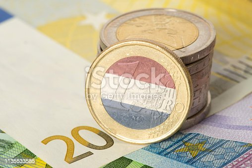 istock Euro notes and coins and flag of Holland 1135533585