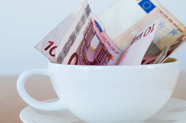 Euro (EUR) Notes in an Empty Coffee Cup Close Up stock photo