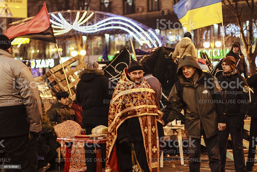 Euromaidan protesters rest. Orthodox priest talks with people royalty-free stock photo