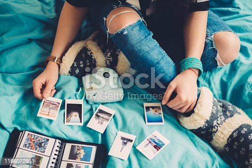 Woman in bed arranging travel photos