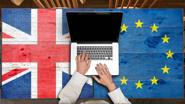 European and UK flagged wooden Table with laptop stock photo