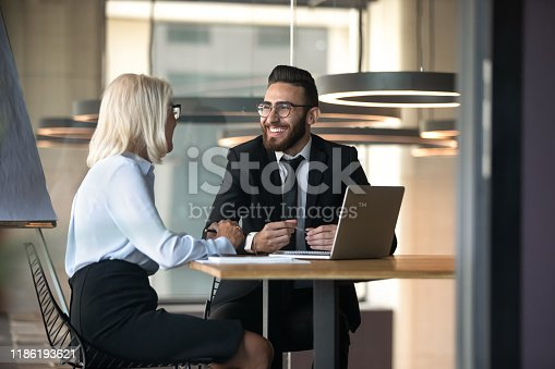 European Arabian business partners negotiating sit at desk hold pens pc notepads on table, diverse client and boss meet for solve issues, plan future cooperation, making profitable proposition concept