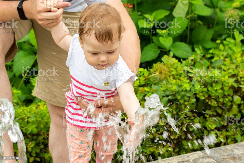European baby girl playing with jets of water in a fountain. Baby...