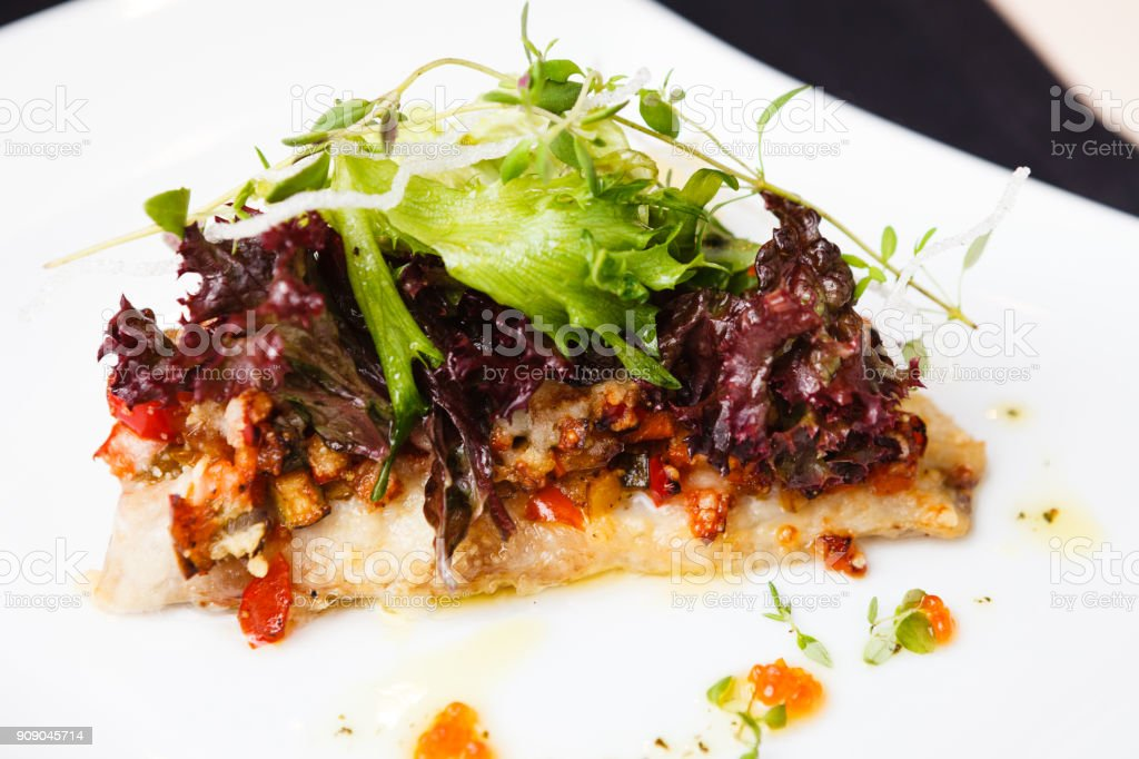 European bass branzino European bass branzino with spicy ratatouille and red caviar Baked Stock Photo