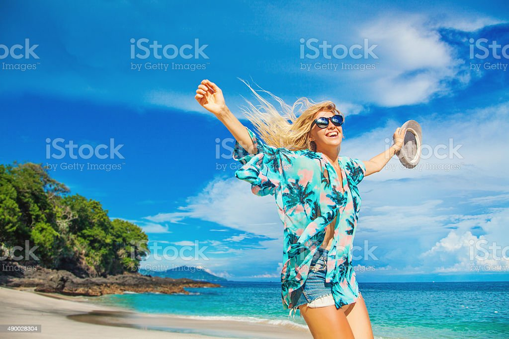 European blond girl jumping on a background of tropical beach stock photo