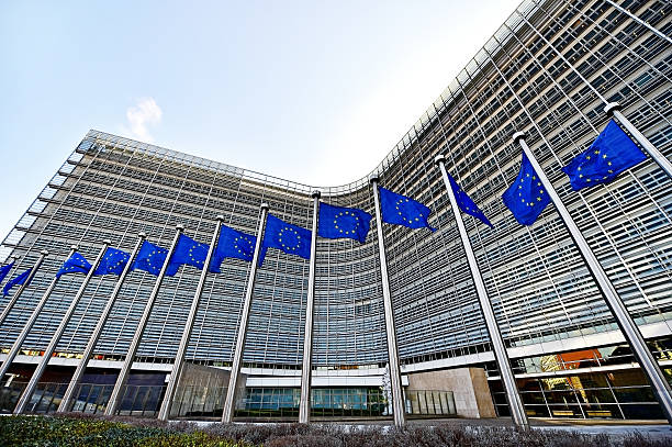European Comission Headquarters Brussels, Belgium - March 16, 2016: EU flags blown by wind in front of the European Commission Headquarters, also know as the Berlaymont building, in Brussels. berlaymont stock pictures, royalty-free photos & images