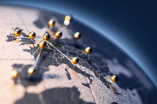 States and capitals of the European Union pinned with golden pins on a cork globe. The pins are connected to each other with a golden thread.