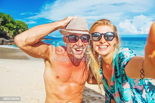 istock European couple smiling and hugging on background of tropical beach 490028556