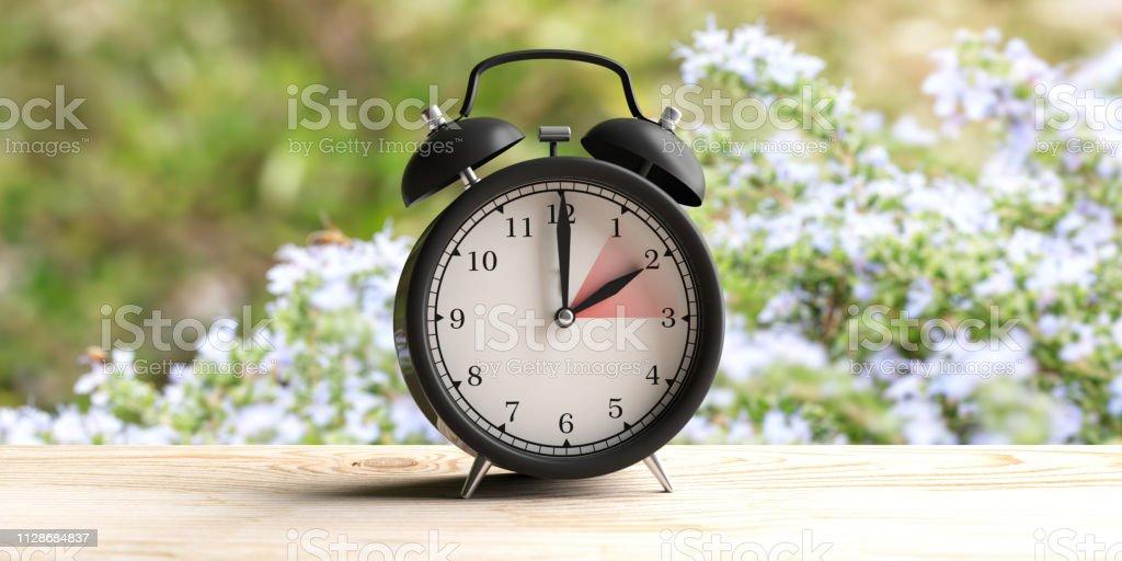 ヨーロッパの夏時間。木製の机の上の時計のアラーム、春、自然の背景をぼかし。3 d イラストレーション ロイヤリティフリーストックフォト