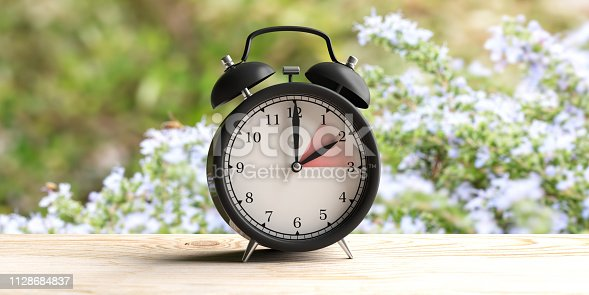 istock European daylight saving time. Alarm clock on wooden desk, blur spring nature background. 3d illustration 1128684837