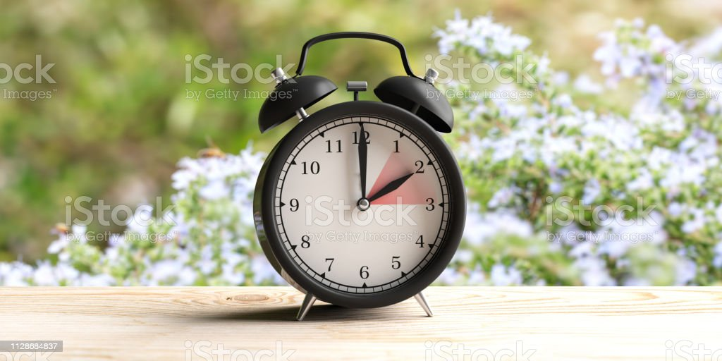 European daylight saving time. Alarm clock on wooden desk, blur spring nature background. 3d illustration stock photo