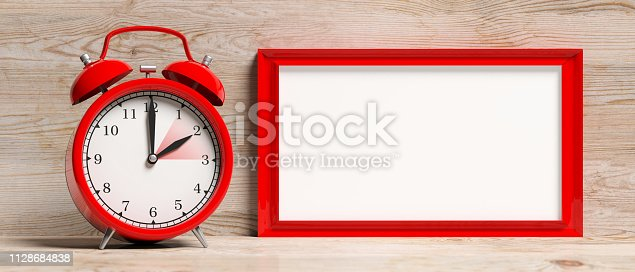 istock European daylight saving time. Red alarm clock and blank frame isolated on wooden background, banner. 3d illustration 1128684838