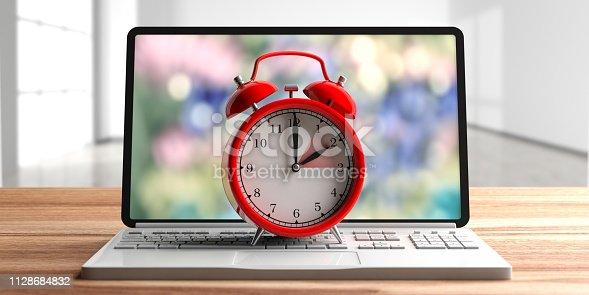 istock European daylight saving time. Red alarm clock on a computer laptop on wooden desk. 3d illustration 1128684832