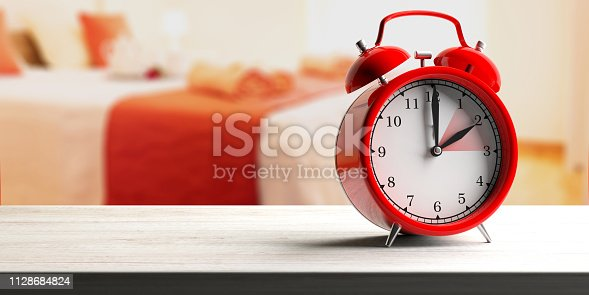 istock European daylight saving time. Red alarm clock on wooden desk, blur bedroom background, banner. 3d illustration 1128684824