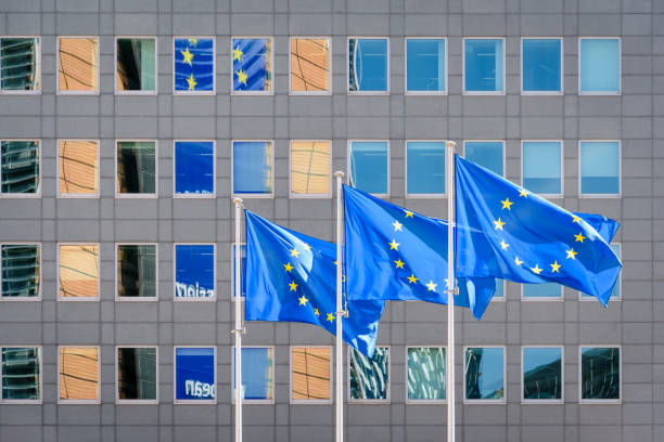 European flags blowing in the wind in front of the European Commission in Brussels, Belgium. Three european flags blowing in the wind at full-mast in front of the Berlaymont building, headquarters of the European Commission, the executive of the European Union (EU) in Brussels, Belgium. european commission stock pictures, royalty-free photos & images