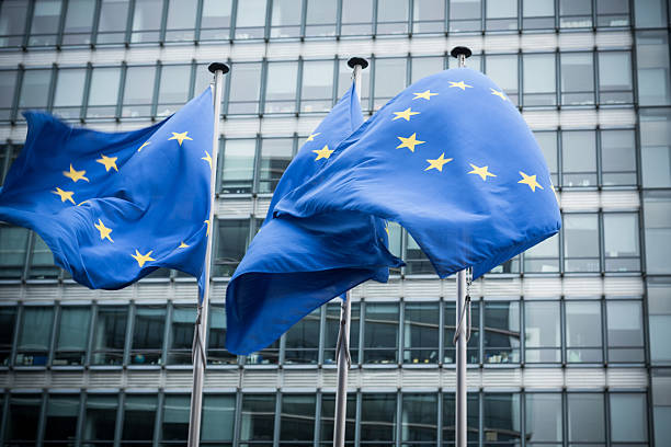"""European flags. """"European flags in front of the European Commission headquarters in Brussels, Belgium. ( Motion Blurred on flags)"""" european union currency stock pictures, royalty-free photos & images"""