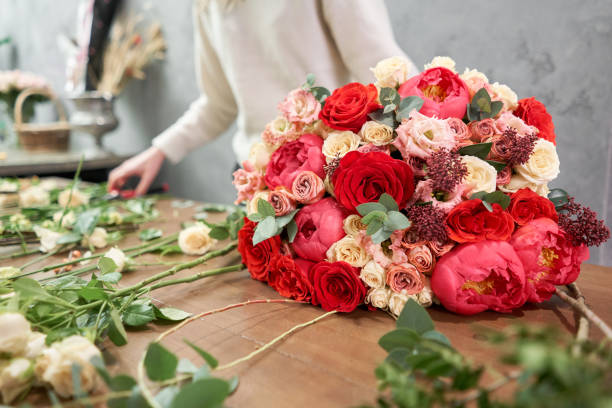 European floral shop concept. Florist woman creates red beautiful bouquet of mixed flowers. Handsome fresh bunch. Education, master class and floristry courses. Flowers delivery. stock photo