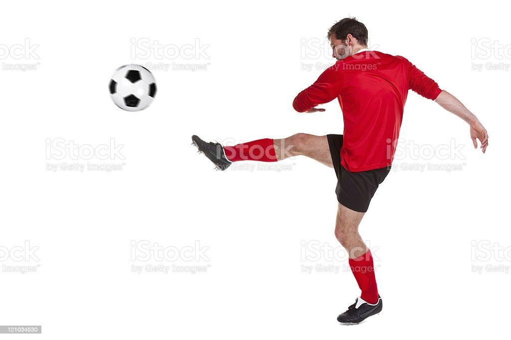 European football player in red uniform kicking a ball stock photo