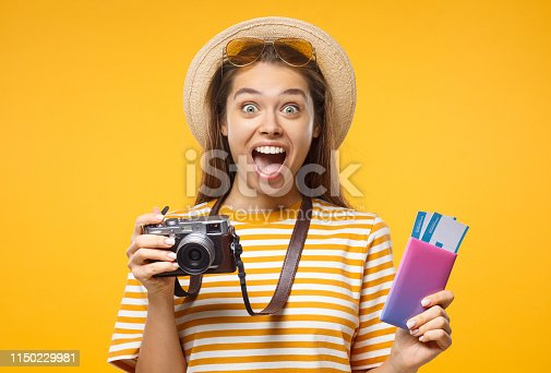 European girl with retro camera, pasport and airplane tickets shocked with good commercial offer, isolated on yellow background