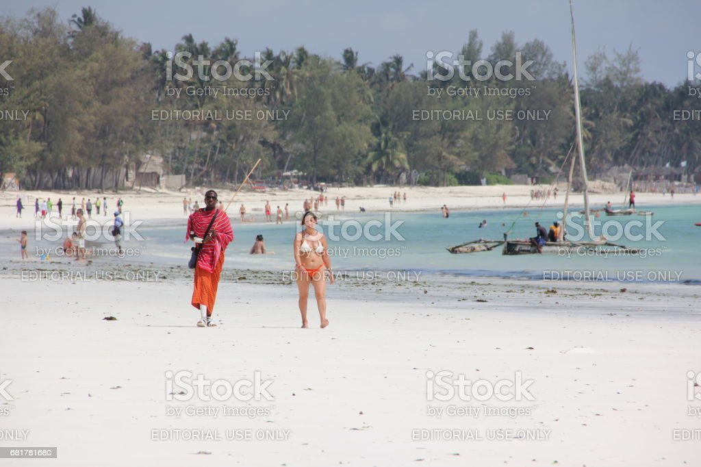 European Lady and Maasai Man walk at the Kiwengwa Beach, Zanzibar, Indian Ocean, Africa stock photo