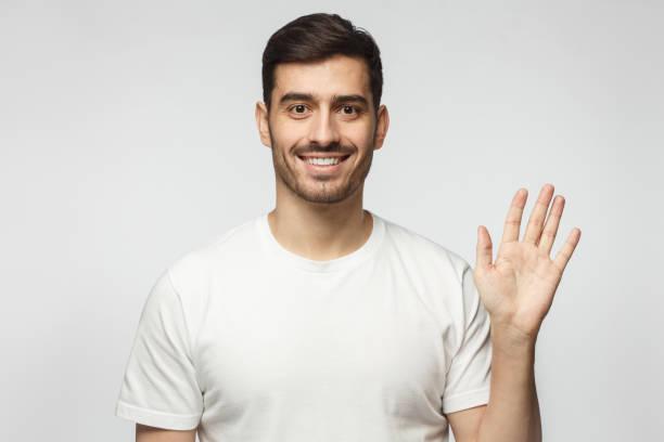 european man greeting someone with open hand, smiling, enjoying communication, isolated on gray background - sventolare la mano foto e immagini stock