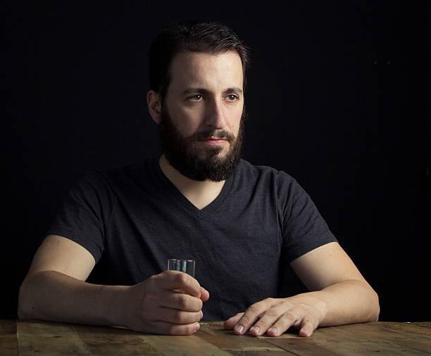Europea hombre sentado en la mesa de madera - foto de stock