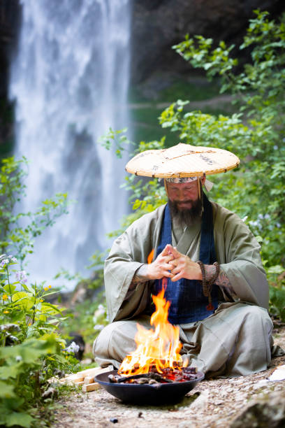 european man with beard and japanese robe makes fire ceremony in front of great waterfall in austria - religious celebration stock photos and pictures