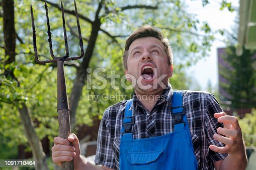 istock European man with pitchfork is angry, losing his mind. 1091710464