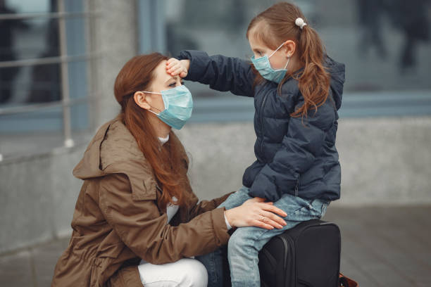 European mothers in respirators with kids are standing near a building stock photo