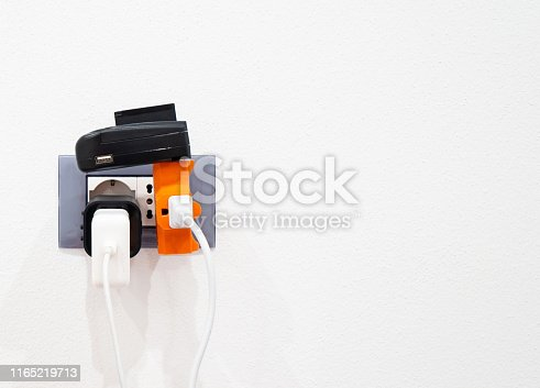 European electric outlet with universal converters and devices plugged into wall.