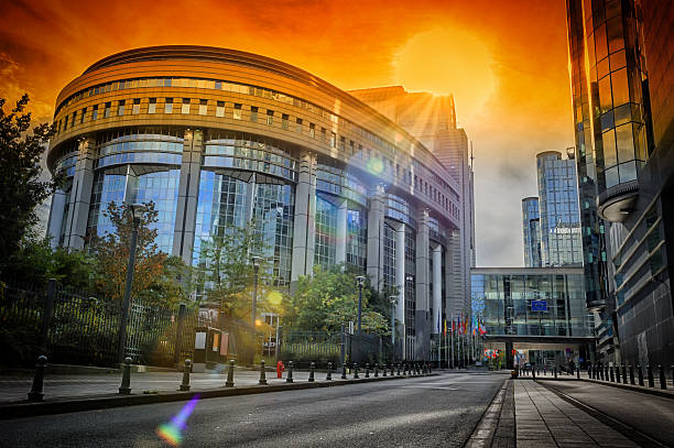 European Parliament building at sunset. Brussels, Belgium European Parliament building at summer orange sunset. Brussels, Belgium european commission stock pictures, royalty-free photos & images
