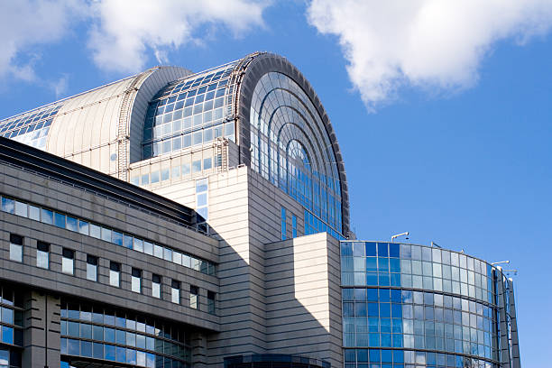 "European Parliament building in Brussels ""Side view of the stylish glass-covered European Parliament building in Brussels, against a blue, clouded sky."" berlaymont stock pictures, royalty-free photos & images"
