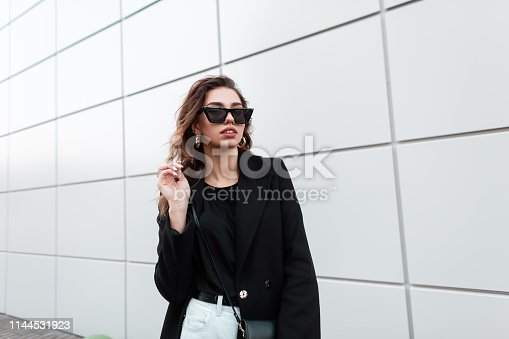 European pretty young hipster woman in trendy sunglasses in a vintage coat in white jeans with a bag stands near a gray building in the city. Beautiful girl for a walk. Stylish women's clothing.