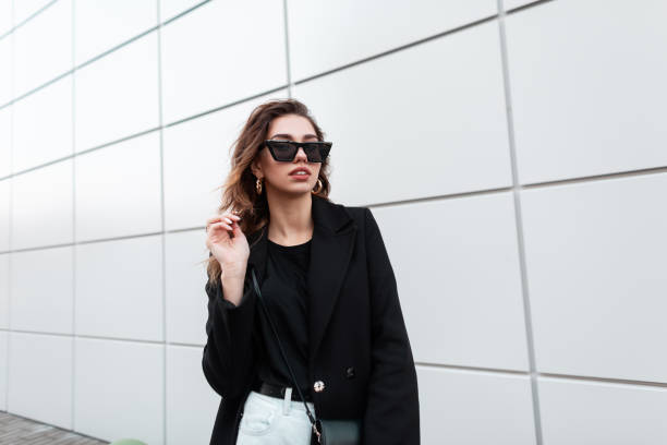 european pretty young hipster woman in trendy sunglasses in a vintage coat in white jeans with a bag stands near a gray building in the city. beautiful girl for a walk. stylish women's clothing. - fashion стоковые фото и изображения