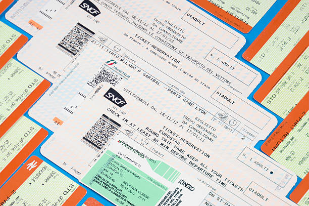 European rail tickets laid on table - Travel background Durham, England - December 17, 2012: the photo includes several used rail tickets belonging to different European Railways; they were photographed in my home on blue background. Yellow-orange tickets: National Rail (U.K.); SNCF: French railways; FS: Trenitalia (Italy); Trenord: Italy train ticket stock pictures, royalty-free photos & images
