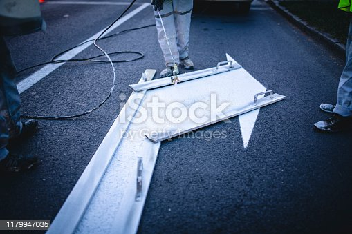 Close-up of Central European infrastructure maintenance crew repainting urban street surface markings at dusk.