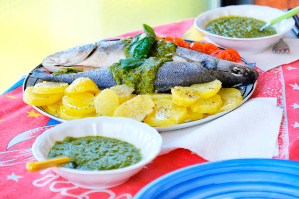 european sea bass branzino steaming potatoes tomatoes basil sauce recipe stock photo