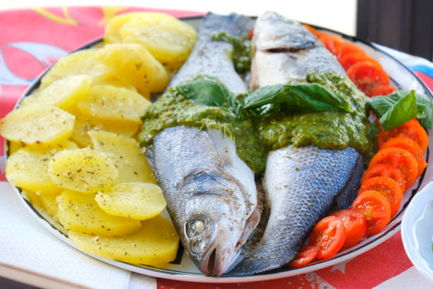european seabass branzino basil sauce recipe closeup stock photo