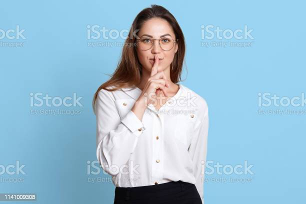 European slender woman shows with gesture to keep in silence, holding forefinger near lips, stands firmly and confidently with her long dark hair down and widely open blue eyes. Copy space for ad.
