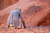 A blonde woman tourist is on her knees exploring and picking desert flowers that bloomed in spring at wadi Rum desert. She wears a skirt and is bare foot on red sand.