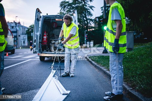 Infrastructure construction crew spray painting road surface marking in European capital city urban street.