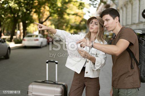 European travelers love couple using a local map on a sunny day. Raises his hand indicates an empty spot. Honeymoon travel, European tourism, or vacation travel concept