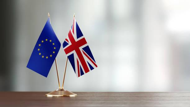 europäischen union und britische flagge paar auf einem schreibtisch über defokussierten hintergrund - britische politik stock-fotos und bilder