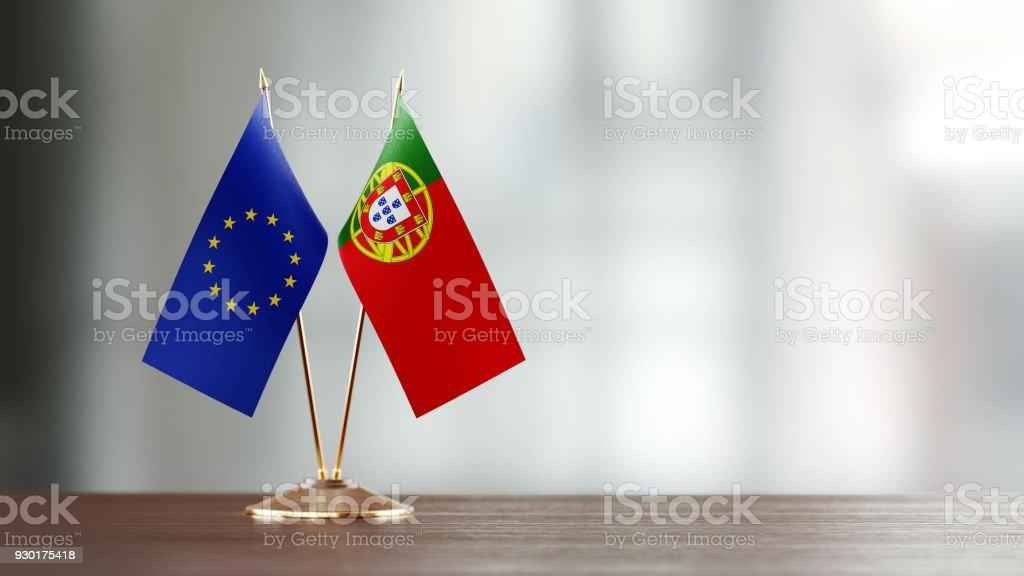 European Union And Portuguese Flag Pair On A Desk Over Defocused Background - fotografia de stock