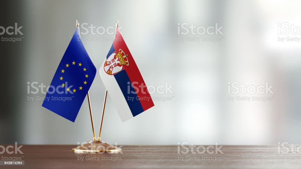 European Union And Serbian Flag Pair On A Desk Over Defocused Background - fotografia de stock