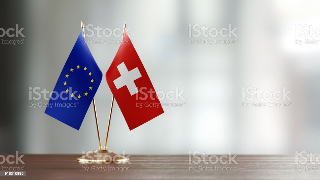 European Union And Swiss Flag Pair On A Desk Over Defocused Background - Foto stock royalty-free di Accanto